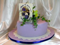 Ordered by a daughter for her mother's 75th birthday. Her request was that it include orchids and the lilies, as those were in her mom's wedding bouquet. Oh, and purple is her favorite color. The cake is cakepro's (thanks, cakepro!) lemon cake recipe (oh, so good!), two layers, torted and filled with lemon curd and fresh raspberry filling. Coated with white choc ganache, covered with white choc/cheesecake MFF. Thanks to Marie Herbstritt for the inspiration for the gum paste card.