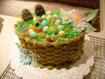 I made this for my boyfriend's family (Easter 2011). Egg-shaped pans from Wilton Course 2 class (2 layer), basket weave, grass tip, gumpaste flowers, store-bought jelly beans and peanut butter eggs. I had a handle made for the cake but it broke when I went to put it on!