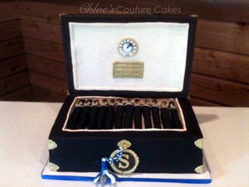 This is a humidor thats chocolate cake with chocolate Ganache and Chocolate SMBC.  The lid is RCT's covered in modeling chocolate and gumpaste.  Hand painted Hygometer, Cigars are chocolate cake rolled in fondant.  Humidor box is covered in Chocolate fondant.  Gumpaste key, tassel and S monogram