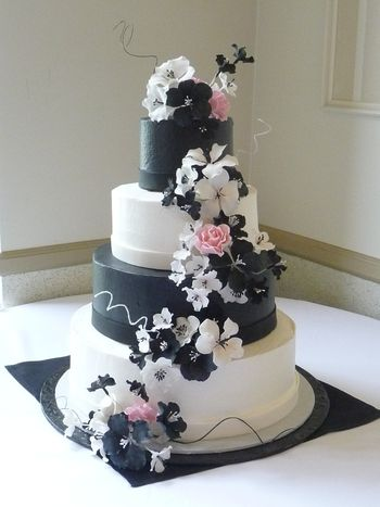 This was inspired by a picture the bride found online. Buttercream frosting with fondant ribbon. Gumpaste flowers.