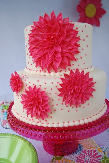 """This cake was for a themed party I hosted for a friend visiting from Europe. Cake is 9"""" and 6"""" with hot pink gumpaste dahlias in different sizes; it's lemon cake with strawberry buttercream covered in fondant. I was inspired by a cake picture that was in a thread in the forums here. The picture wasn't credited so I don't know who the cake designer is. I had already made the large dahlia, just didn't know what I wanted to do with it until I saw that cake. TFL! **UPDATE** Picture was from The Knot; baker no longer in business. Thanks, vpjane, for that info!**"""