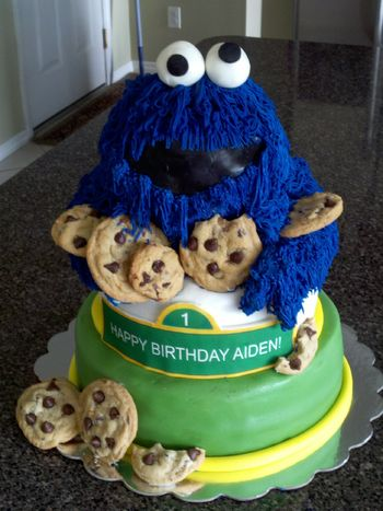 Cookie monster cake made with wilton ball pan and put on a 6 inch carved body and larger bottom tier.