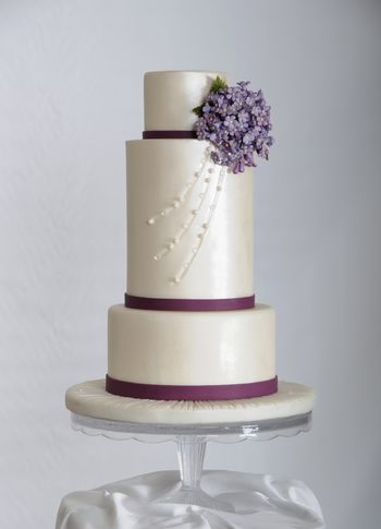 """This cake was featured in the September issue of Cake Central Magazine, in the Less is More, Violet Charm section.  I am so honored and still excited to be asked to contribute to the magazine.  8"""", double 6"""" and 4"""" tiers covered in fondant, adorned with edible pearls and diamonds.  The little bouquet of flowers are gum paste.  TFL"""