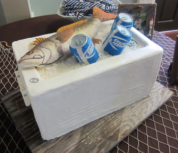 The ice chest is red velvet cake on the top half, the bottom half is a cake dummy. The fish is RKT covered with fondant and hand-painted. The beer cans are RKT covered with fondant. The labels are sugar sheets and the lids are molded fondant. The ice is rock candy.