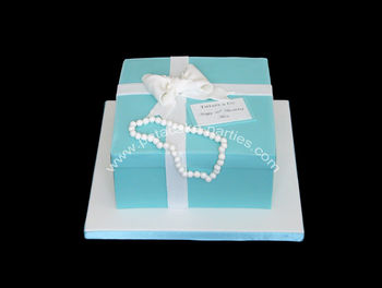"8"" vanilla sponge cake with jam and buttercream covered with marzipan and sugarpaste.  Bow and hand-rolled pearls made from modelling paste.  Edible image for 'card'."