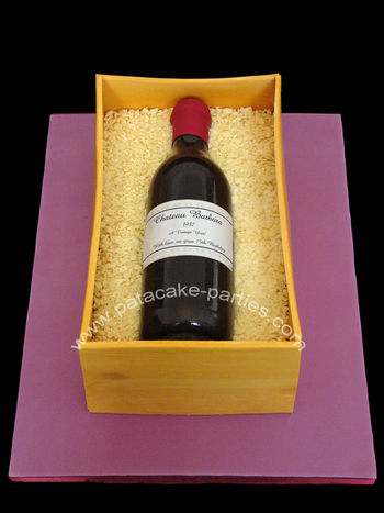 "Wine Bottle in box/crate for my wonderful mother-in-law's 75th birthday luncheon today.  It's a 12"" x 7"" rich fruit cake covered in marzipan and then the box panels were a 50/50 mix of pastillage and modelling paste.  The bottle is entirely sugar (flower paste and modelling paste), with several layers of glaze and an edible image for the personalised label.  The packaging is chopped white chocolate cigarellos.  Next time, I would leave the panels of the box *even longer* to dry before fixing to the cake, because it was only after they'd been in place a few hours that I saw they had bowed slightly.  :o("
