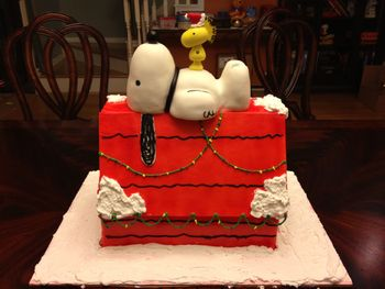 The doghouse is made out of vanilla butter cake with eggnog-flavored buttercream, covered in fondant.  Snoopy is RKT covered in fondant and Woodstock is gumpaste.  All credit for the design goes to jenbakescakes.  I'm still in the early stages of this hobby, and thus sincerely flattering others by imitation.  ;)