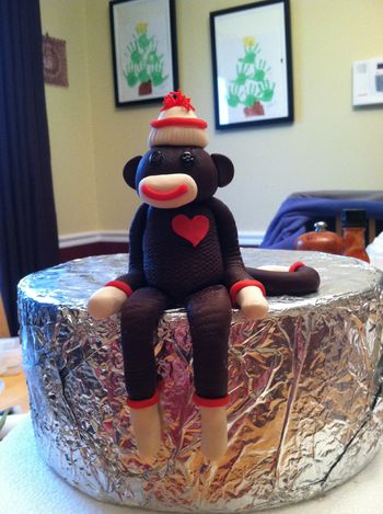 I made this gumpaste sock monkey following a youtube video I watched fhttp://www.youtube.com/watch?v=03jpbL2Ljfs difference is I pressed in texture with a new sponge, I used an extruder, made buttons for the eyes and added a heart.