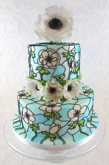 Anemone themed 'stained glass' wedding cake. This is a display cake for this springs wedding fayres. The sugar flower on top is wired with seed head stamens and the ones on the middle of the cake are totally edible. The flowers on the cake where drawn on free-hand using pictures of real flowers for reference and painted on using edible dusts and gels mixed with confectioners glaze.