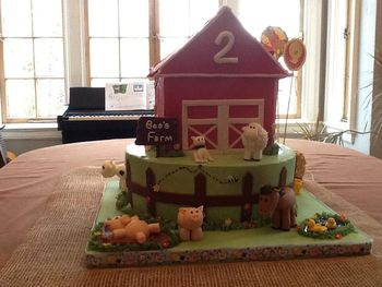 Bottom tier is yellow cake with raspberry filling and SMBC, top tier (barn) is chocolate with SMBC.  All animals handmade from fondant with tylose.  Barn is a bit wonky, but I certainly learned how NOT to put together a barn cake, which is to stay up until 4:32 a.m. holding a roof in place to dry for 32 minutes.  :)