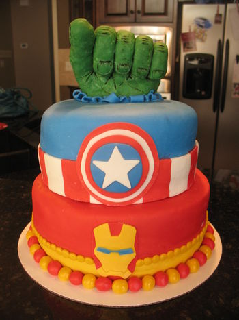 The Avengers Cake Hulk fist made from rice krispie treats covered in modeling chocolate, details painted in food coloring. Iron Man and Captain America details in fondant. www.thecrumbcoat.wordpress.com