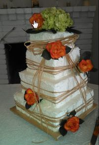 """A 4 tier Square Wedding Cake (12"""", 10"""", 8"""", & 6""""). Chocolate cake with chocolate mousse filling, and White cake with vanilla mousse filling, all covered in buttercream icing. The bride provided the raffia and the fresh flowers that were added on location."""