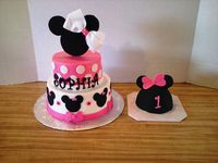 Minnie Mouse Cake: White cake with 6 & 8 inch tiers with Vanilla icing. Decorations are fondant. Topper handcut from foamboard with a real hair bow for the birthday girl made to match the cake.  Mouse Ears Smash Cake: Cake baked in 4 inch stainless steel salad bowl. White cake with Vanilla icing covered with fondant.