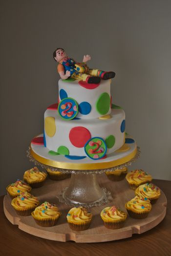 A two-tier cake with a Mr Tumble theme for twins' second birthday.