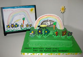 For her 6th birthday, Madeleine wanted a rabbit with a carrot in a flower garden. I asked her to paint me a picture of what she had in mind so I could replicate it in cake. Every picture she draws contains a rainbow, so using flowed sugar for the figures, and pastillage for the rainbow & sun, here is what I came up with. It took more effort to make the wobbly rainbow and crossed lines pencil effect in the rabbit than I thought it would. The cake is strawberry with dark chocolate ganache filling, covered with white chocolate cheesecake MFF.