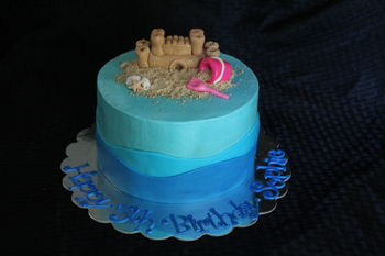 "Sandcastle and sea shells with bucket and shovel in the sand.  8"" round 4 layer cake covered in buttercream with marshmallow fondant waves and hand sculpted decorations.  Sand is cookie crumbs."