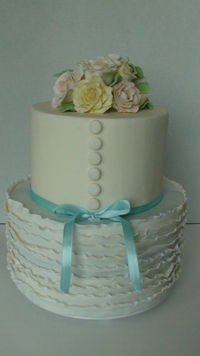 Bridal shower cake that mimics a wedding dress and bouquet. Gumpaste roses and fondant ruffles.