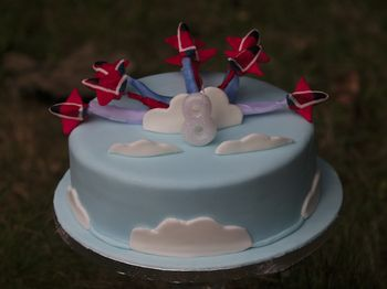 A Red Arrows birthday cake for my son.  We were on holiday so it's not as good as I'd hoped but he was happy with it.  I had to use ribbon for the vapour trails as couldn't source any candy floss in the right colours.  Modelling chocolate planes.