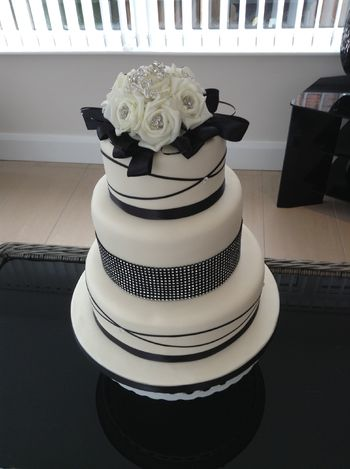 ivory and black 3 tier wedding cake ,top tier zesty lemon,middle tier chocolate and bottom tier Victoria sandwich