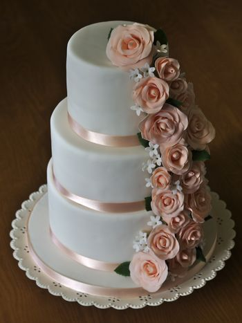 A three-tier birthday cake with sugarpaste roses and filler flowers cascading down the side.