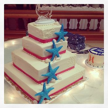 4 tier buttercream wedding cake with handmade starfish and seashells