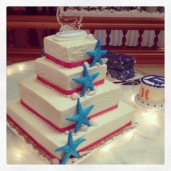 4 tier buttercream wedding cake with handmade starfish and seashells
