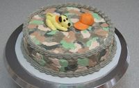 camo cake with fondant puppy & hat.  First error was using SMBC, should have used AMBC.  The icing wouldn't press down smooth, it just got sticky.  Live & learn.  I'll try it again later. Actually I don't want to eat this, it's too ugly.  I just want to put it in the wash machine with some Tide detergent.