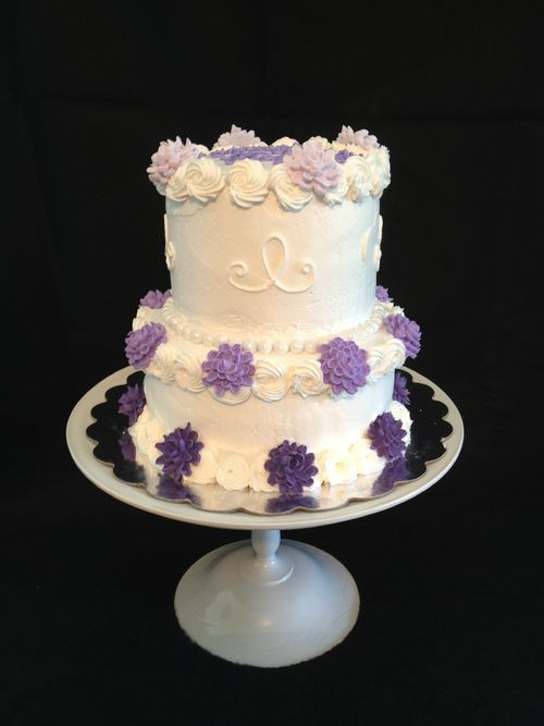 """This is a 2 tiered cake.  The bottom layer is an 8""""  classic white cake and the top tier is a 6"""" chocolate cake, made from scratch recipe.  The icing is a light, creamy buttercream with a rosette boarder.  Edible pearls surround the boarder of the top and bottom layers like jewelry.  The chrysanthemum flowers are piped with royal icing and placed on the cake in an ombre color style.  The cake is displayed on a cake stand crafted by myself from odd glassware and painted white."""