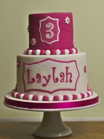 Laylah's Birthday Cake. Vanilla pink ombre cake with vanilla buttercream on the bottom and chocolate cake with chocolate buttercream on the top. White chocolate ganache and sugarpaste to cover.