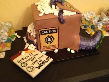 This was a cake for my son's 11th birthday.  He was having a mad scientist party, and we decided this might be a good way to represent the theme.  He's ordered a new pet to take over the world!  WASC (which is his favorite), with a standard american buttercream. The box sides and top are modeling chocolate (first time working with it--pretty intriguing), and the tentacles are fondant.  Packing peanuts are marshmallows, obviously.  Images are on edible paper/edible ink.  Thanks for looking!