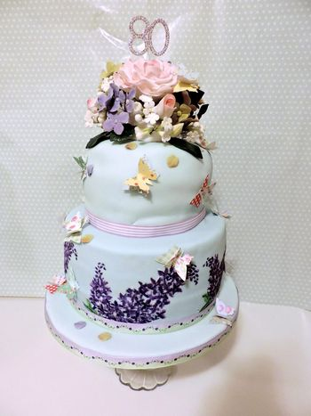 Made with love for my mum's 80th birthday, bottom tier is vanilla and strawberry cake with strawberry buttercream, top tier is peach cake with peach buttercream (big issue with bulging but never mind)  handmade gumpaste roses, hydrangeas, filler flowers on top, paper butterflies glued on with a bit of royal icing and on the bottom tier I hand painted lilacs.