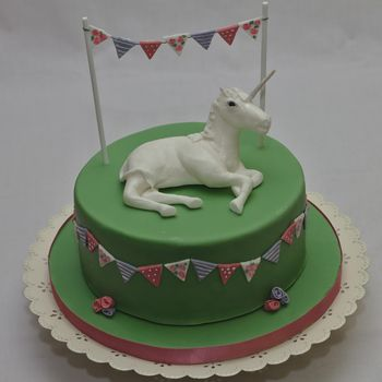 A gluten-free chocolate cake with a sugarpaste unicorn on top and hand-painted bunting.