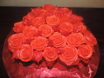 Red velvet cake with cream cheese buttercream icing.  The roses are made with vanilla buttercream icing and placed on red floral foil.
