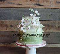 Green ombre ruffles with gumpaste dogwoods and leaves on this pretty little cake.