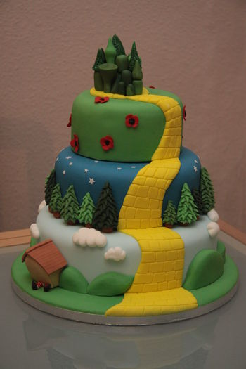Wizard of Oz themed wedding cake including Munchkin Land, the Dark Forest, the poppy fields and the Emerald City and complete with Witch crushed by a house!