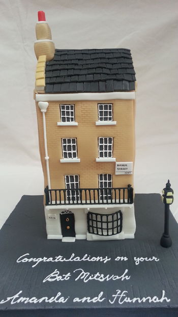 A house cake made of chocolate cake and Smbc. The cake bulged at the sides which is why the walls are wonky.  Bay window and balcony made of royal icing, everything else is fondant and gumpaste. The roof is RKT inside.
