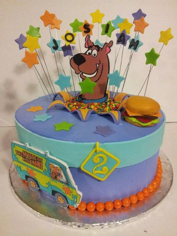 "11"" round frosted in Pastry Pride. Stars, Scooby and the mystery machine van are edible images mounted on a gumpaste plaque. Cheeseburger is fondant and dog collar is modeling chocolate"