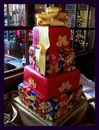 This was my challenge cake in 2013.  Gold sugar lace pieces - handcut and airbrushed gold.  Extra large gold sugar bow, purple, burgundy and red stripes.  The bride handed me a piece of wrapping paper and asked that I make the cake look exactly like it.  Had such a headache ...... but I smiled for a week in the afterglow.  :-)