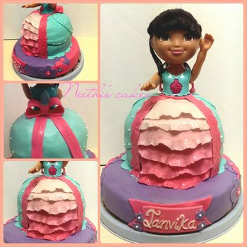 """Dora cake"" A doll cake made for a Dora themed birthday party.  -The bottom 9 in cake tier is made with chocolate chip cake -The dress cake is made with a yellow- chocolate chip cake. The cake is decorated using homemade MMF and chocolate butter-cream frosting.  The dress is made using teal colored MMF and the ombre frills are made using gradient colored MMF."
