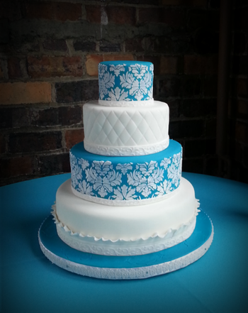 I recently did this wedding cake for the son of a friend.  The bride didn't want a topper or anything else, but I'd have liked a large peony or rose on top.  The fondant is Albert Uster FondArt, a product that I love.  I matched the blue to David's Bridal Malibu Blue.  The damask is royal icing stenciling.  The embossed ribbon is a new product from Wilton and I love it--deep embossing, flexible, and very time saving.