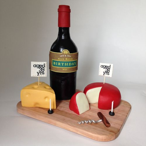Standing wine bottle was cake, covered in black fondant. Neck of the bottle is RCT.  Cheese is cake covered in fondant.  The white part of the gouda is modeling chocolate. Cork screw is chocolate fondant on top, gumpaste for the coil, painted with silver highlighter dust.  Party was for 2 husbands, one turning 38 the other turning 39.