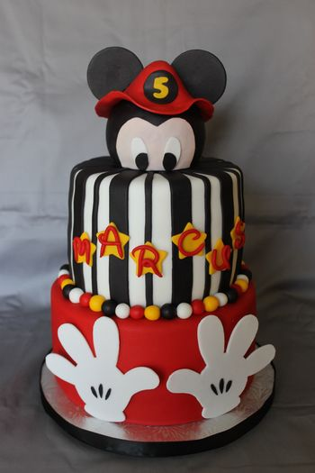 I used a styrofoam ball for the head and covered it in fondant. The fireman hat was made with gum paste, and so were the hands on the bottom tier.