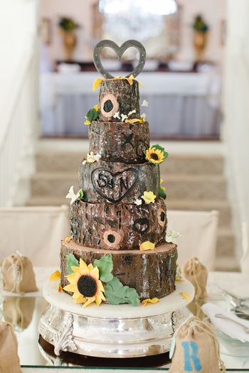 "Tree trunk; tree bark; sunflowers.  Rustic. Country.  Barn wedding.   I wrote to CC to see what's wrong:  I cannot enter a single word to thank you for your awesome comments or explain what I did!!  First of all, I used chocolate ganache on the sides and white ganach on the tops.  Go to the Winbeckler site, CakeSuppliesPlus.com and order the ""Tree Bark Texture Mat Silicone"" for $22.  I don't know how you could get this texture otherwise.  Site says it works for buttercream (I tried and agree but wanted ganache) and fondant (would agree but didn't try).  Procedure:  Dust the mold heavily with ""poof"" (1/2 cornstarch; 1/2 confex sugar) because you DO want the white to stay on the ganache for the effect.  Then thin black, brown (s), mossy green(s), and white/beige with extract, vodka, or, my favorite,  peppermint schnapps (!).  Notice that each layer is an experiment, but what generally worked best was black with a small, thin brush in the deepest recesses, vey thin white with a wide, course  brush lightly over the highest points (up and down was better than sideways), and brown(s) and green(s) randomly applied.  Cake topper by BlacksmithCreations on Etsy.  Board covered  with burlap.  ""Carving"" by dipping a very small ball tool in hot water then wiping dry; melted the ganache perfectly.  Sunflower inspiration by Edna - I love her - De La Cruz.  I am very glad to give further insight and/or answer questions as soon as CC allows me to do so!!"