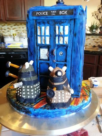 Battle worn Tardis fights against the Daleks . . . chocolate cake covered in homemade modeling chocolate and cupcake daleks