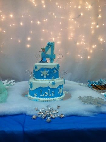Blue raspberry cake, buttercream iced with fondant snowflakes & topper. Elsa toy figurine.