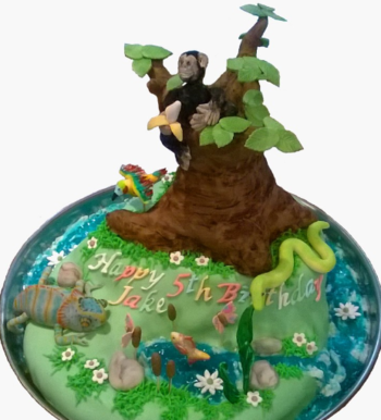 Wildlife themed cake with lake,waterfall and river, a chimpanzee sitting in a rkt baobab tree eating a banana, a chameleon, a bird, a green mamba, a fish, reed and grass with flowers and butterflies, rocks and a fish.