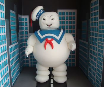 My first standing 3d figure is the giant Marshmallow man from the Ghostbusters movie. It was a big learning curve for me. The upper part of the torso is cake, the underside is Styrofoam. The head is RKT. He's meant to look evil but I couldn't quite get that look on his face. Everything else is fondant. I printed out buildings on paper and glued to a cardboard box to surround the figure on 3 sides. The cake is for my friend's son who is turning 6.