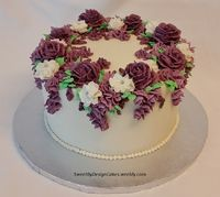 "8"" vanilla almond cake with buttercream flowers in shades of purple and white."