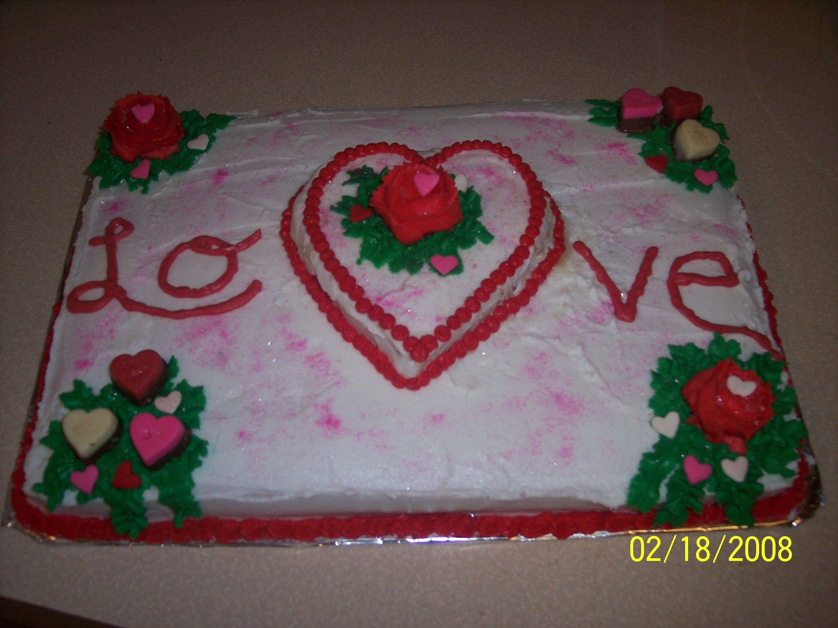 9x13 white cake with a small heart made out of white cake in center. Iced in buttercream with buttercream roses, heart sprinkles, pink luster, edible glitter and milk chocolate hearts.