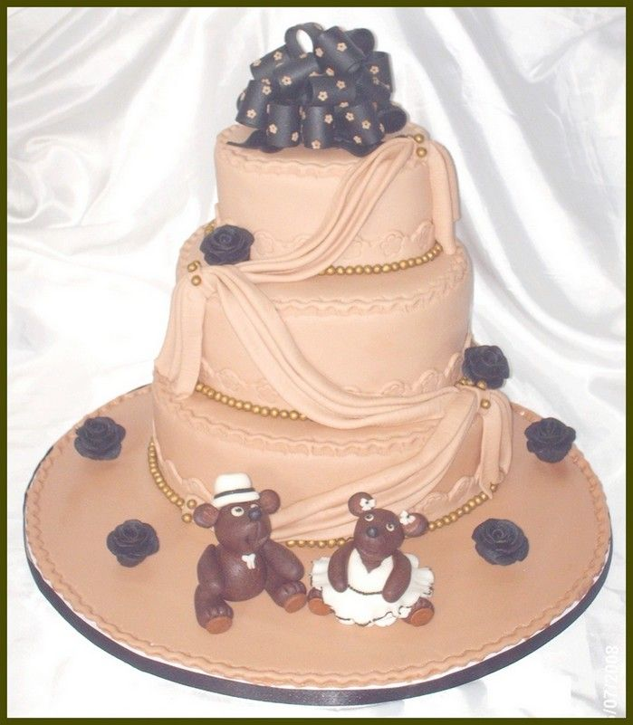 This is a three tier cake covered with mmf. The drapes & beads are also from mmf.The bow topper, black roses & teddies are from gumpaste.